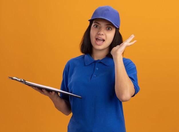 Jeune livreuse en uniforme bleu et cap holding clipboard smiling être surpris debout sur un mur orange