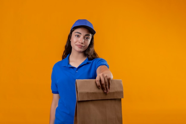 Jeune livreuse en uniforme bleu et cap holding paper package looking at camera avec sourire confiant sur le visage debout sur fond jaune
