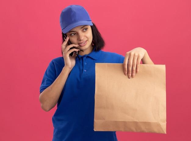 Jeune livreuse en uniforme bleu et cap holding paper package parler sur téléphone mobile avec sourire sur le visage debout sur le mur rose