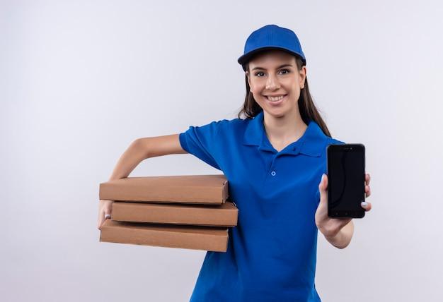 Jeune livreuse en uniforme bleu et cap holding pile de boîtes de pizza montrant smartphone regardant la caméra en souriant joyeusement