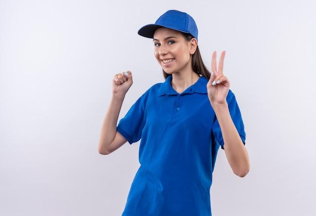 Jeune livreuse en uniforme bleu et cap serrant le poing montrant le signe de la victoire