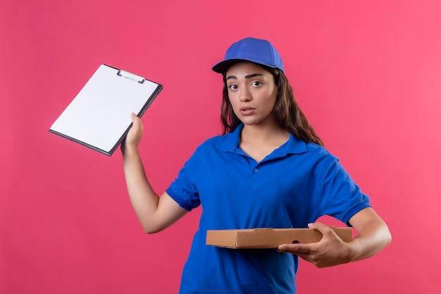 Jeune livreuse en uniforme bleu et cap tenant des boîtes de pizza montrant le presse-papiers à la recherche anxieux debout sur fond rose