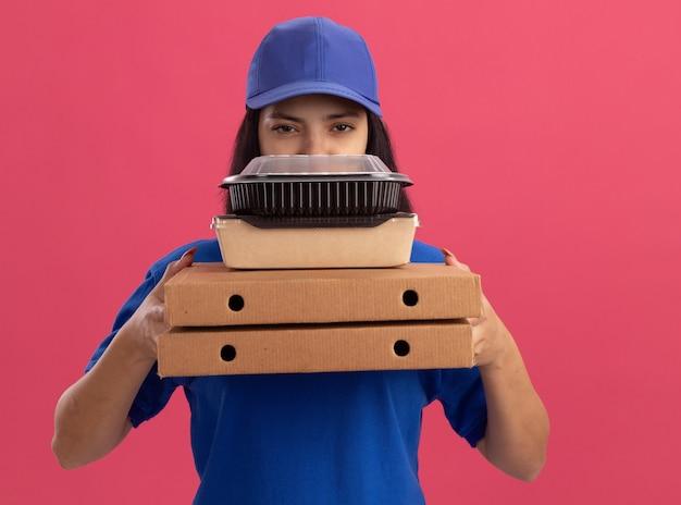 Jeune livreuse en uniforme bleu et cap tenant des boîtes à pizza et un paquet alimentaire avec un visage sérieux debout sur un mur rose