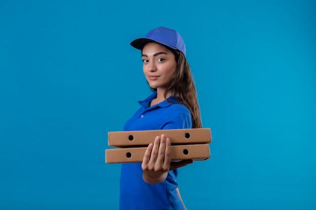 Jeune livreuse en uniforme bleu et cap tenant des boîtes à pizza regardant la caméra souriant confiant heureux et positif debout sur fond bleu