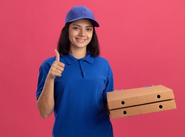 Jeune livreuse en uniforme bleu et cap tenant des boîtes à pizza souriant avec visage heureux montrant les pouces vers le haut debout sur le mur rose