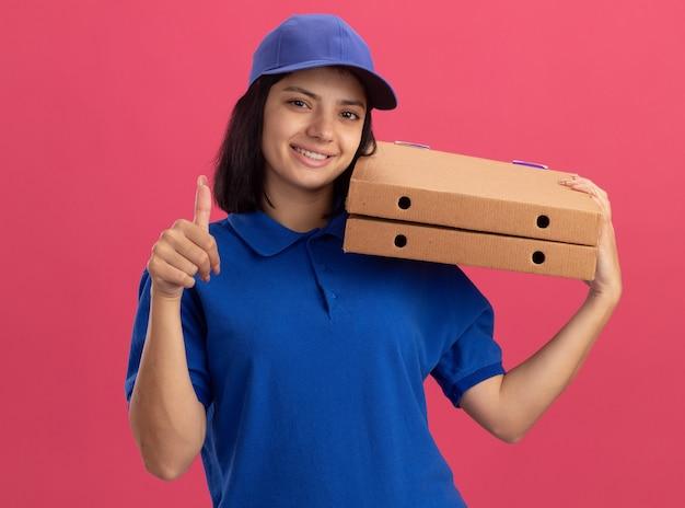 Jeune livreuse en uniforme bleu et cap tenant des boîtes à pizza avec visage heureux montrant les pouces vers le haut debout sur le mur rose
