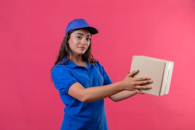 Jeune livreuse en uniforme bleu et cap tenant un paquet de boîte à un client souriant debout sur fond rose