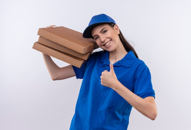 Jeune livreuse en uniforme bleu et cap tenant pile de boîtes de pizza regardant la caméra en souriant joyeusement montrant les pouces vers le haut