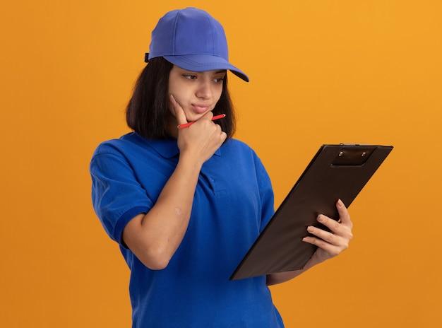 Jeune livreuse en uniforme bleu et cap tenant le presse-papiers en le regardant avec une expression pensive debout sur un mur orange
