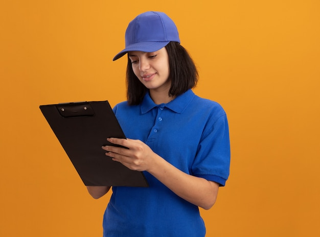 Jeune livreuse en uniforme bleu et cap tenant le presse-papiers en le regardant avec le sourire sur le visage debout sur le mur orange