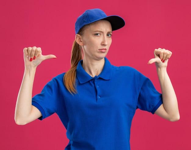 Jeune livreuse en uniforme bleu et casquette avec une expression sceptique se montrant elle-même debout sur un mur rose