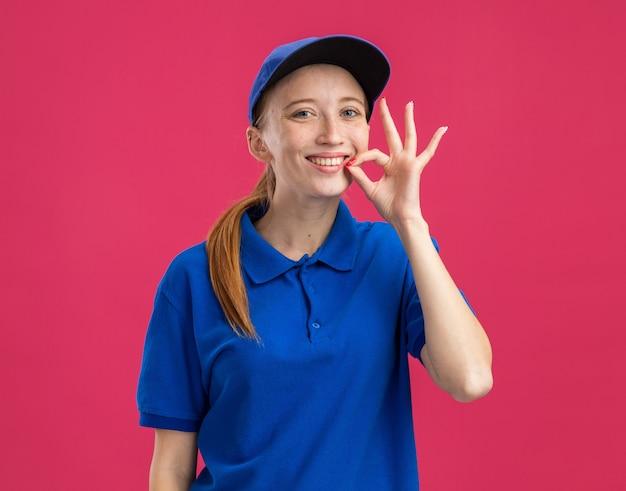 Jeune livreuse en uniforme bleu et casquette heureuse et joyeuse faisant un geste de silence comme fermer la bouche avec une fermeture éclair