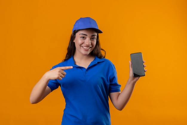 Jeune livreuse en uniforme bleu et casquette montrant smartphone pointant avec le doigt vers elle souriant confiant regardant la caméra debout sur fond jaune