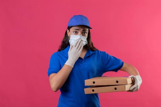 Jeune livreuse en uniforme bleu et casquette portant un masque de protection du visage et des gants tenant des boîtes de pizza à la bouche surprise et choquée couvrant avec la main debout sur fond rose
