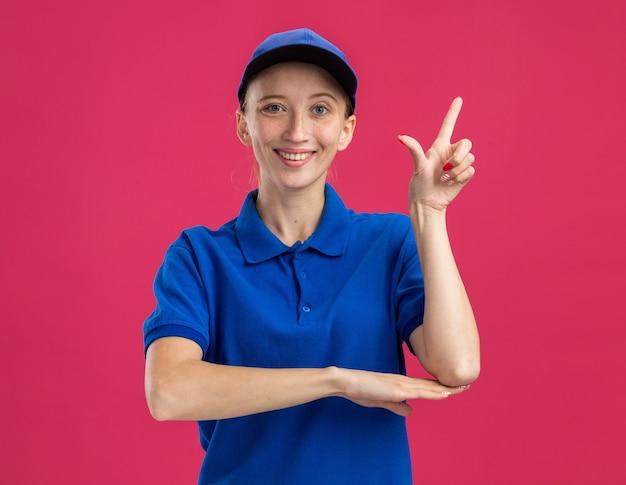 Jeune livreuse en uniforme bleu et casquette souriante confiante montrant l'index debout sur le mur rose