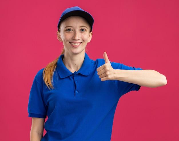 Jeune livreuse en uniforme bleu et casquette souriante confiante montrant les pouces vers le haut debout sur le mur rose