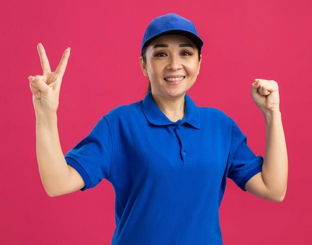 Jeune livreuse en uniforme bleu et casquette souriante montrant gaiement le signe v serrant le poing debout sur le mur rose