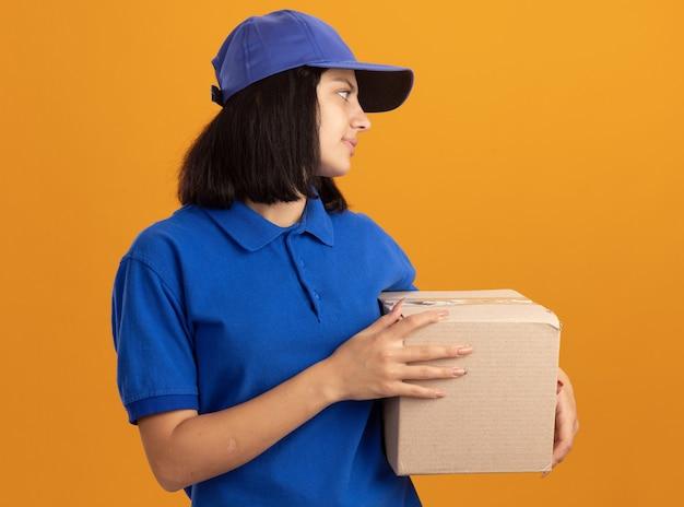 Jeune livreuse en uniforme bleu et casquette tenant une boîte en carton à côté souriant sympathique debout sur un mur orange