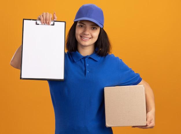 Jeune livreuse en uniforme bleu et casquette tenant une boîte en carton montrant le presse-papiers avec des pages vierges souriant debout confiant sur le mur orange