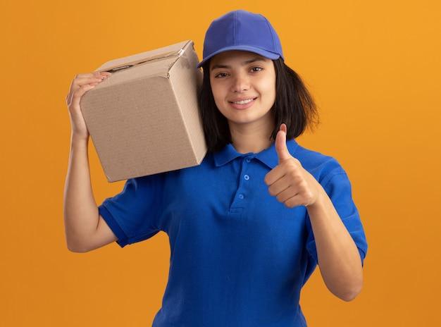 Jeune livreuse en uniforme bleu et casquette tenant une boîte en carton sur son épaule smilin montrant les pouces vers le haut debout sur un mur orange