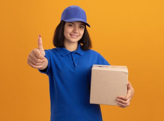 Jeune livreuse en uniforme bleu et casquette tenant une boîte en carton souriant joyeusement montrant les pouces vers le haut debout sur un mur orange