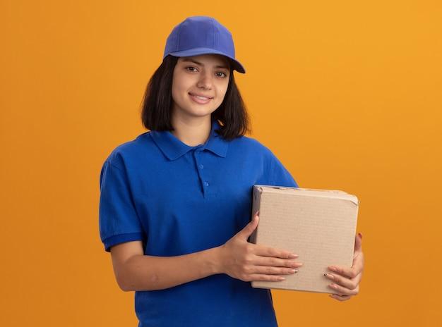 Jeune livreuse en uniforme bleu et casquette tenant une boîte en carton souriant sympathique debout sur un mur orange