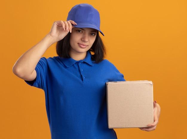 Jeune livreuse en uniforme bleu et casquette tenant une boîte en carton avec un sourire confiant sur le visage debout sur un mur orange