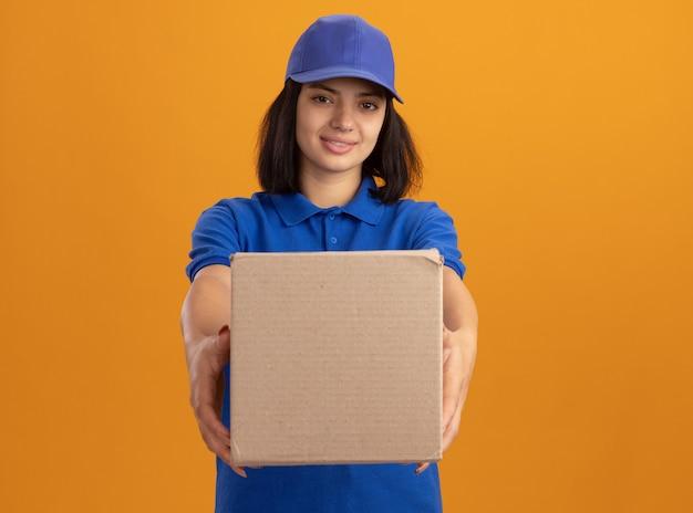 Jeune livreuse en uniforme bleu et casquette tenant une boîte en carton avec sourire sur le visage debout sur un mur orange