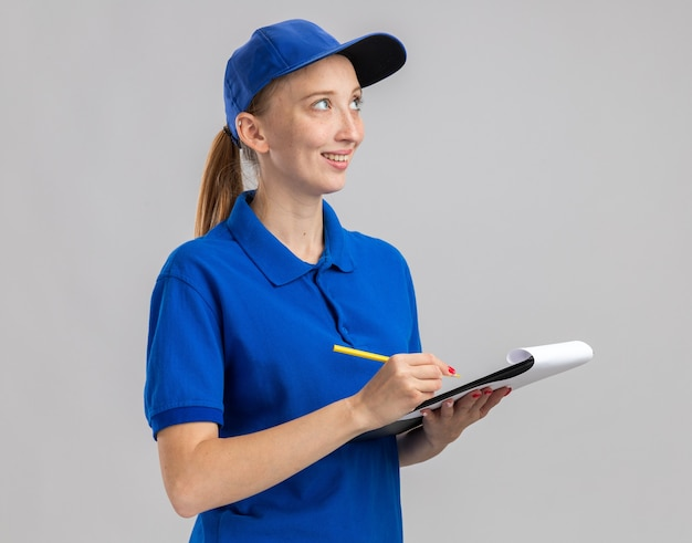 Jeune livreuse en uniforme bleu et casquette tenant un crayon et un presse-papiers avec des pages blanches regardant de côté avec un sourire sur le visage
