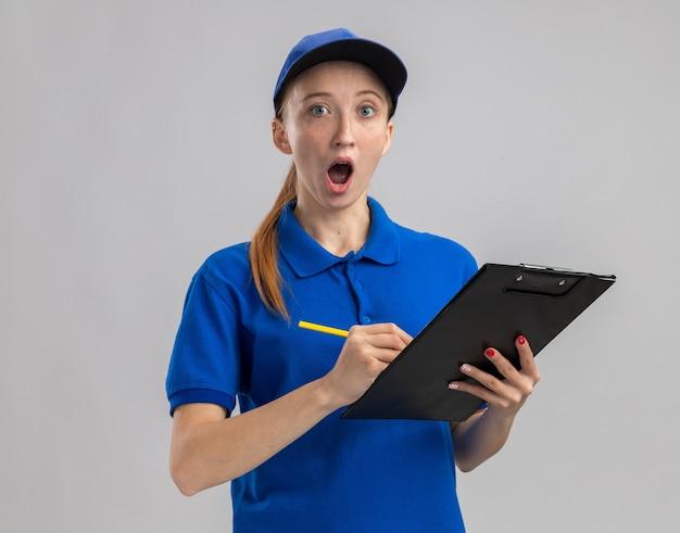 Jeune livreuse en uniforme bleu et casquette tenant un presse-papiers et un crayon semblant surpris d'écrire quelque chose debout sur un mur blanc