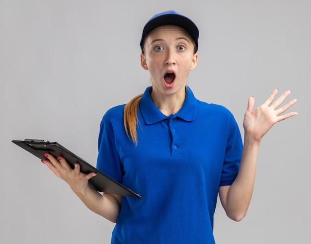 Jeune livreuse en uniforme bleu et casquette tenant le presse-papiers étonné et surpris