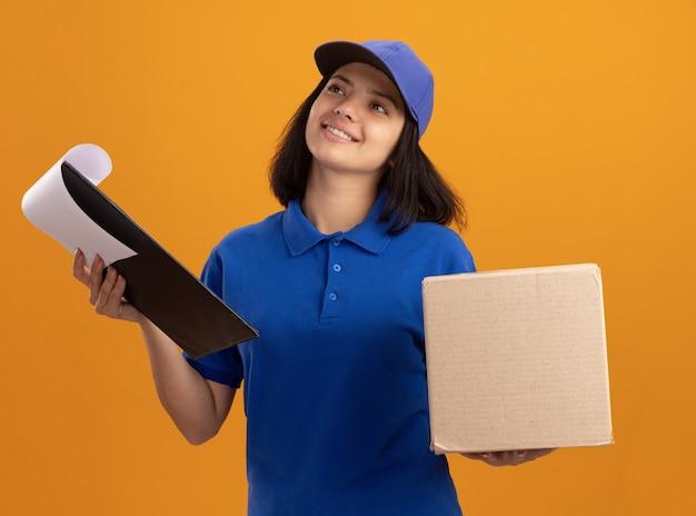Jeune livreuse en uniforme bleu et casquette tenant le presse-papiers avec des pages blanches et une boîte en carton à la recherche avec un visage heureux souriant debout sur un mur orange