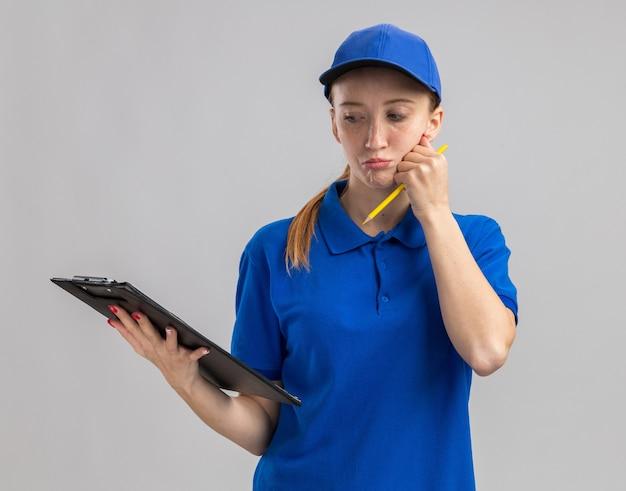 Jeune livreuse en uniforme bleu et casquette tenant le presse-papiers en le regardant avec un visage sérieux pensant