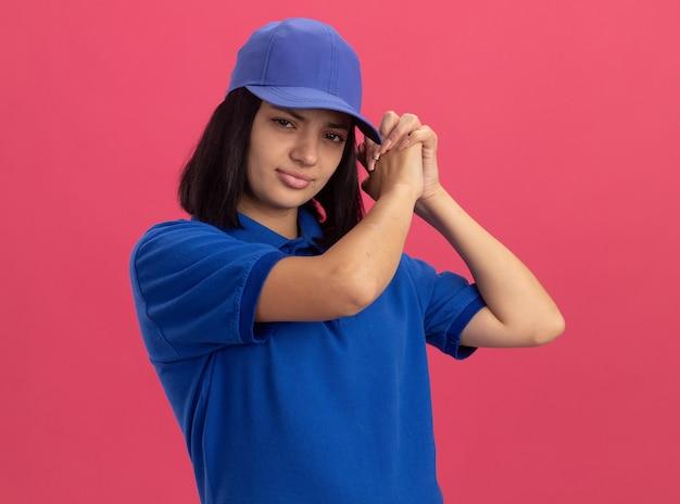 Jeune livreuse en uniforme bleu et casquette avec visage sérieux faisant le geste de l'équipe debout sur le mur rose