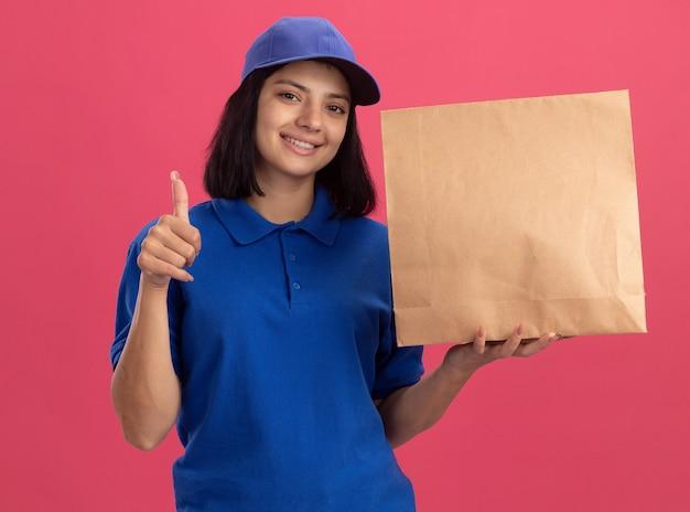 Jeune livreuse en uniforme bleu et chapeau montrant le paquet de papier souriant confiant montrant les pouces vers le haut debout sur le mur rose