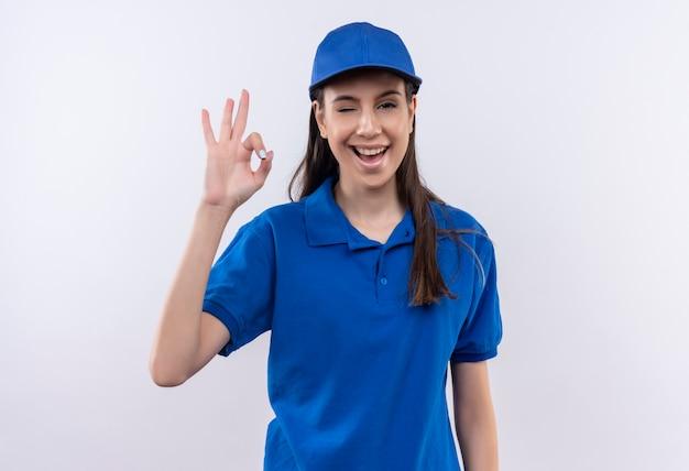Jeune livreuse en uniforme bleu et chapeau souriant et un clin de œil confiant montrant signe ok