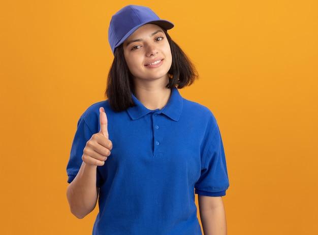 Jeune livreuse en uniforme bleu et chapeau souriant sympathique montrant les pouces vers le haut debout sur le mur orange