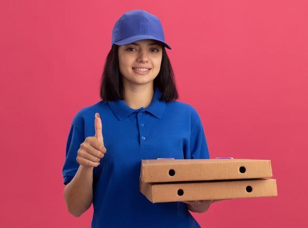Jeune livreuse en uniforme bleu tenant des boîtes à pizza montrant les pouces vers le haut souriant sympathique debout sur le mur rose