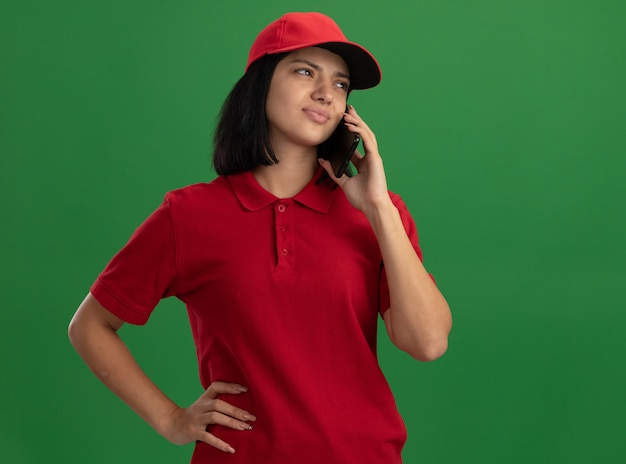 Jeune livreuse en uniforme rouge et cap à la confusion et anxieux tout en parlant au téléphone mobile debout sur le mur vert