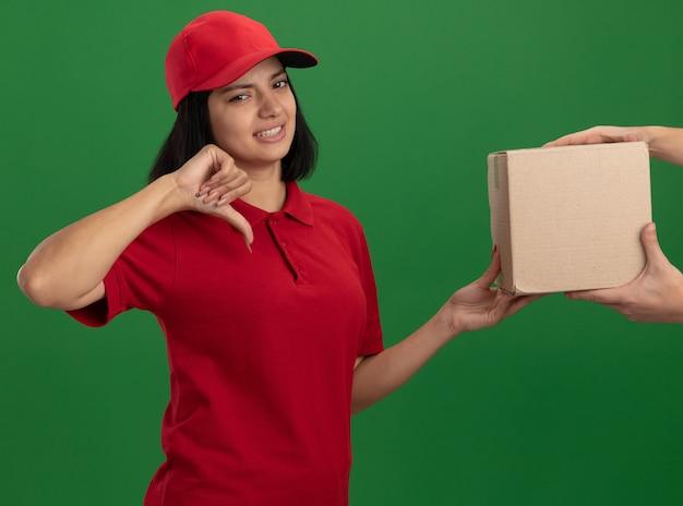 Jeune livreuse en uniforme rouge et cap holding boîte en carton à un client à la mécontentement montrant les pouces vers le bas debout sur le mur vert