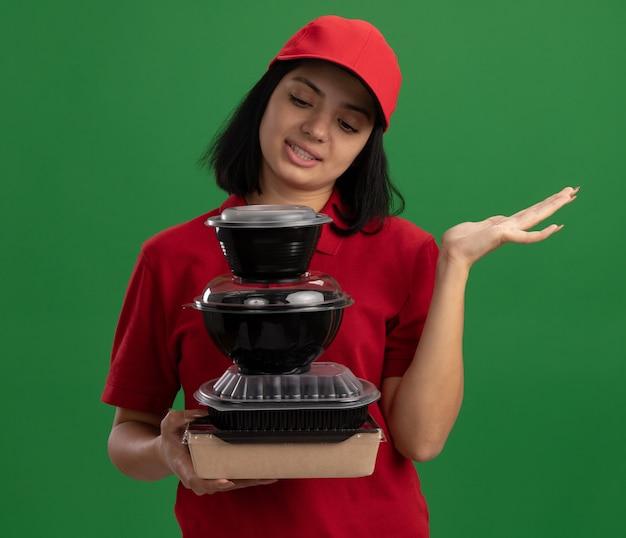 Jeune livreuse en uniforme rouge et cap holding pile de colis alimentaires à la recherche de confus avec bras levé debout sur mur vert