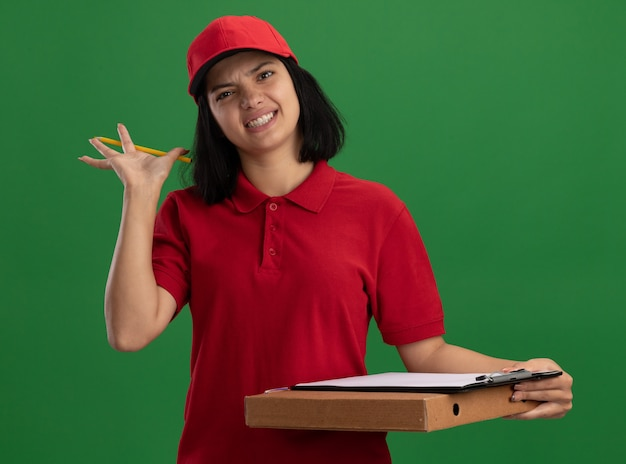 Jeune livreuse en uniforme rouge et cap tenant la boîte à pizza et le presse-papiers avec un crayon avec une expression agacée debout sur un mur vert
