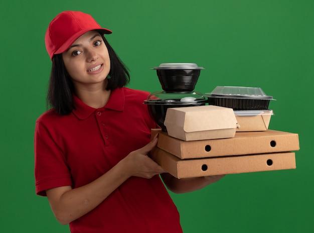 Jeune livreuse en uniforme rouge et cap tenant des boîtes de pizza et des emballages alimentaires souriant debout confus sur mur vert