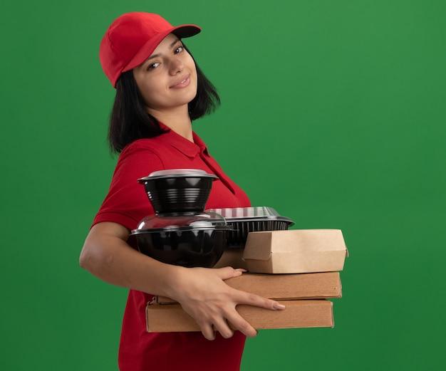 Jeune livreuse en uniforme rouge et cap tenant des boîtes de pizza et des emballages alimentaires souriant avec un visage heureux debout sur un mur vert