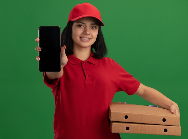 Jeune livreuse en uniforme rouge et cap tenant des boîtes à pizza montrant smartphone avec sourire sur le visage debout sur un mur vert