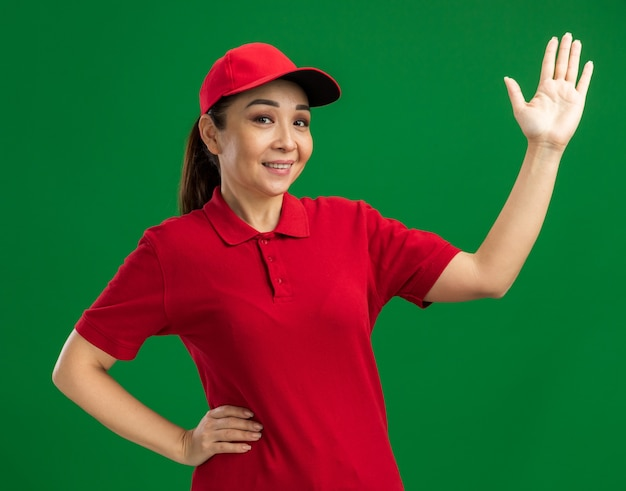 Jeune livreuse en uniforme rouge et casquette heureuse et positive levant la main souriant joyeusement debout sur un mur vert
