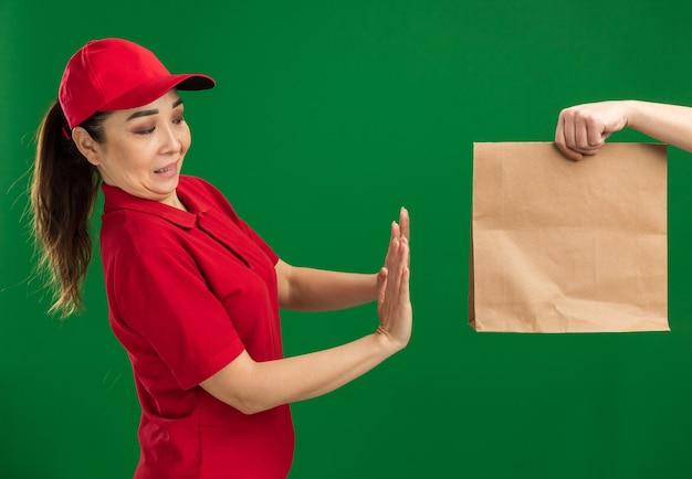Jeune livreuse en uniforme rouge et casquette refusant de recevoir un paquet de papier debout sur un mur vert