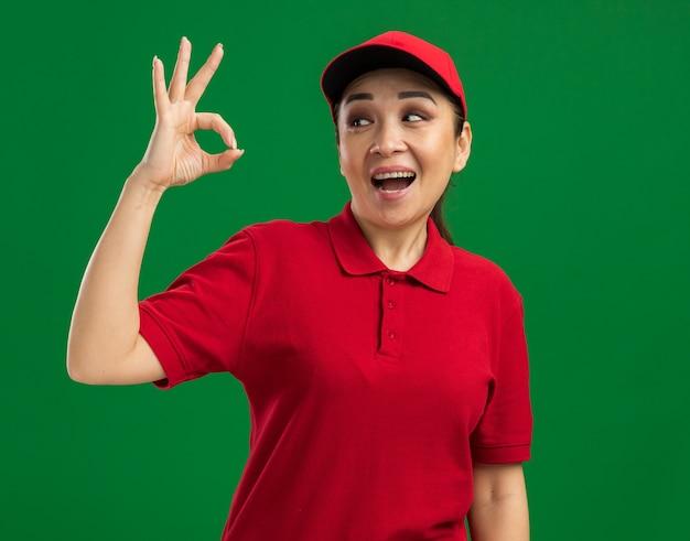 Jeune livreuse en uniforme rouge et casquette regardant de côté heureuse et joyeuse faisant signe ok debout sur un mur vert