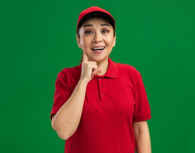 Jeune livreuse en uniforme rouge et casquette souriante heureuse et joyeuse debout sur un mur vert