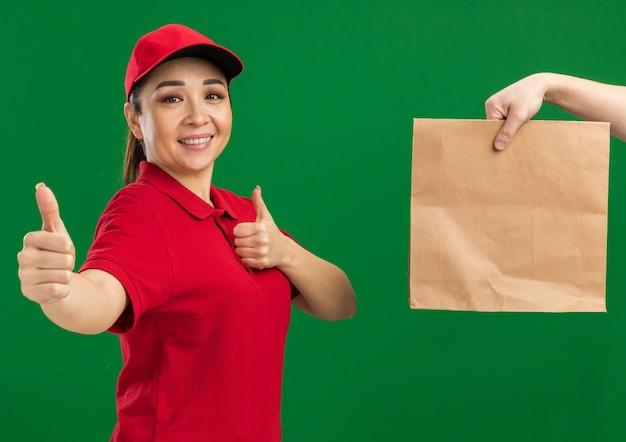 Jeune livreuse en uniforme rouge et casquette souriante montrant les pouces vers le haut tout en recevant un paquet de papier debout sur un mur vert